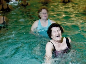 Two older women in a swimming pool exercising