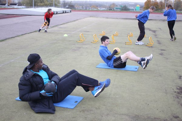 One student is doing stomach crunches with Harry Aikines-Aryeetey. Two other students are jumping hurdles,