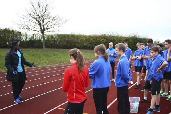 Harry talking to the students on the running track. A box of equipment is in the picture too
