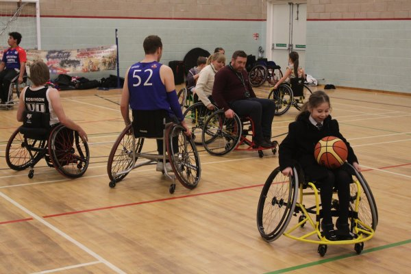People playing wheelchair basketball. One of the players has the basketball on her lap